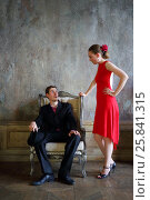 Купить «Beautiful girl in red dress and man pose near armchair in old retro room», фото № 25841315, снято 4 июня 2015 г. (c) Losevsky Pavel / Фотобанк Лори