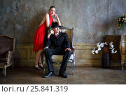 Купить «Girl in red dress and man in black suit pose near armchair in old room», фото № 25841319, снято 4 июня 2015 г. (c) Losevsky Pavel / Фотобанк Лори