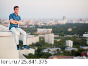 Купить «Young man in denim clothes sits crossing arms on chest on the edge of the building roof», фото № 25841375, снято 4 июня 2015 г. (c) Losevsky Pavel / Фотобанк Лори