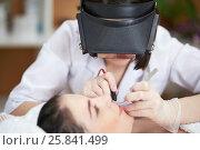 Купить «Beautician in magnifying lenses does epilation on upper lip of woman lying on couch in beauty salon», фото № 25841499, снято 1 марта 2015 г. (c) Losevsky Pavel / Фотобанк Лори