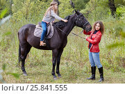 Купить «Woman in red jacket holds by the bridle horse on whom her daughter sits», фото № 25841555, снято 13 сентября 2015 г. (c) Losevsky Pavel / Фотобанк Лори