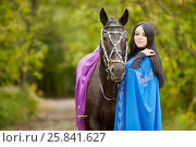 Купить «Black-haired smiling woman in blue capote stands with bay horse in the park», фото № 25841627, снято 13 сентября 2015 г. (c) Losevsky Pavel / Фотобанк Лори