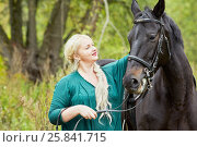 Купить «Blonde woman with plait in green clothes and chestnut horse in park», фото № 25841715, снято 13 сентября 2015 г. (c) Losevsky Pavel / Фотобанк Лори