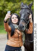 Купить «Young black-haired woman makes selfie with horse in park», фото № 25841759, снято 13 сентября 2015 г. (c) Losevsky Pavel / Фотобанк Лори