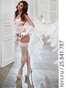 Young woman in white underwear, stockings and angel wings behind her back in room against doorway. Стоковое фото, фотограф Losevsky Pavel / Фотобанк Лори