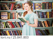 Купить «Young woman in green dress reads book, standing at library», фото № 25841803, снято 7 марта 2015 г. (c) Losevsky Pavel / Фотобанк Лори