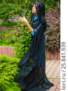 Middle age woman in black sari and Indian adornment walks in summer park. Стоковое фото, фотограф Losevsky Pavel / Фотобанк Лори