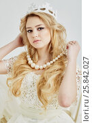 Купить «Young blond woman in crown holds beads of big artificial pearls around her neck», фото № 25842027, снято 7 марта 2015 г. (c) Losevsky Pavel / Фотобанк Лори