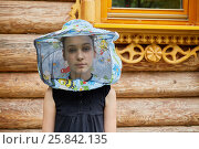 Купить «Teenage girl in hat with bee veil stands against wooden house», фото № 25842135, снято 18 июня 2016 г. (c) Losevsky Pavel / Фотобанк Лори