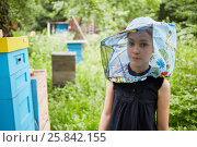 Купить «Teenage girl in hat with bee veil stands at apiary near beehives», фото № 25842155, снято 18 июня 2016 г. (c) Losevsky Pavel / Фотобанк Лори