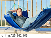 Купить «Young man in denim clothes lies in hammock mounted to fencing of building roof», фото № 25842163, снято 12 июня 2015 г. (c) Losevsky Pavel / Фотобанк Лори