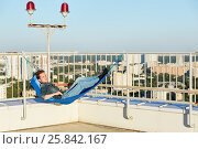 Купить «Young man in denim clothes lies in hammock mounted to fencing of building roof», фото № 25842167, снято 12 июня 2015 г. (c) Losevsky Pavel / Фотобанк Лори