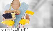 Купить «Woman in apron with brushes against blurry grey room», фото № 25842411, снято 16 сентября 2019 г. (c) Wavebreak Media / Фотобанк Лори