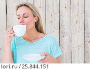 Купить «Woman drinking from white cup against white wood panel», фото № 25844151, снято 25 мая 2020 г. (c) Wavebreak Media / Фотобанк Лори