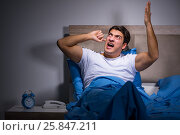 Купить «Young man struggling from noise in bed», фото № 25847211, снято 28 декабря 2016 г. (c) Elnur / Фотобанк Лори