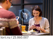 Купить «couple with smartphones and zodiac signs at cafe», фото № 25860007, снято 17 ноября 2016 г. (c) Syda Productions / Фотобанк Лори