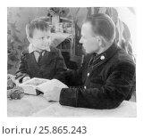 Купить «Отец разговаривает с сыном, сидя за столом перед открытой книгой. Мужчина и мальчик смотрят друг на друга (винтажное фото 1954 год)», фото № 25865243, снято 27 мая 2019 г. (c) Ольга Коцюба / Фотобанк Лори