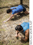 Купить «Fit man and woman crawling under the net during obstacle course», фото № 25872127, снято 24 ноября 2016 г. (c) Wavebreak Media / Фотобанк Лори