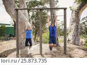 Купить «Fit man and woman performing pull-ups on bar during obstacle course», фото № 25873735, снято 24 ноября 2016 г. (c) Wavebreak Media / Фотобанк Лори