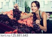 Купить «Young female seller holding bunch of grapes», фото № 25881643, снято 21 января 2020 г. (c) Яков Филимонов / Фотобанк Лори
