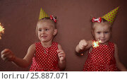 Купить «Two charming little sisters twins in holiday caps with sparkling Bengal lights in their hands having fun on a holiday», видеоролик № 25887071, снято 12 января 2017 г. (c) Mikhail Davidovich / Фотобанк Лори
