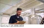 Купить «men with clipboard at brewery or beer plant», видеоролик № 25898859, снято 30 марта 2017 г. (c) Syda Productions / Фотобанк Лори