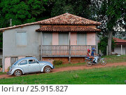 Купить «Motorcycle and fusca traveling in front of the typical house in the district of Curralinho, Diamantina, Minas Gerais, Brazil, 01.2016», фото № 25915827, снято 1 января 2016 г. (c) age Fotostock / Фотобанк Лори