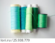 Купить «green and blue thread spools on table», фото № 25938779, снято 29 сентября 2016 г. (c) Syda Productions / Фотобанк Лори