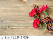 9 мая. Праздничный фон - три красные гвоздики и георгиевская лента на деревянном фоне с местом для текста, фото № 25941039, снято 2 апреля 2017 г. (c) Зезелина Марина / Фотобанк Лори
