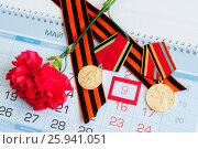 Купить «Натюрморт - две юбилейные медали в честь Победы в Великой Отечественной войне, красная гвоздика и георгиевская лента на календаре с датой 9 мая», фото № 25941051, снято 8 апреля 2017 г. (c) Зезелина Марина / Фотобанк Лори