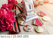 Купить «Натюрморт на День Победы - старинный металлический настольный календарь с датой 9 мая, медали, георгиевская лента, букет красных гвоздик. Концепция 9 мая», фото № 25941055, снято 8 апреля 2017 г. (c) Зезелина Марина / Фотобанк Лори