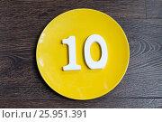 Купить «Number ten on a yellow plate», фото № 25951391, снято 23 марта 2017 г. (c) Григорий Алехин / Фотобанк Лори