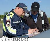 Купить «Инспектор дорожно-патрульной службы полиции оформляет протокол о нарушении», фото № 25951475, снято 14 мая 2016 г. (c) Free Wind / Фотобанк Лори