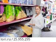 Купить «Pretty shop assistant offers to choose pet food», фото № 25955295, снято 24 января 2020 г. (c) Яков Филимонов / Фотобанк Лори