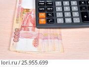Купить «Российские деньги и калькулятор лежат на столе», фото № 25955699, снято 11 апреля 2017 г. (c) Максим Мицун / Фотобанк Лори