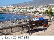 Купить «Пожилая пара сидит на скамейке и смотрит на пляж и океан. Город Costa Adeje, Тенерифе, Канарские острова, Испания», фото № 25967915, снято 31 декабря 2015 г. (c) Кекяляйнен Андрей / Фотобанк Лори