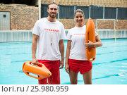 Купить «Two lifeguards standing with rescue buoy at poolside», фото № 25980959, снято 12 декабря 2016 г. (c) Wavebreak Media / Фотобанк Лори