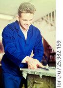 Купить «guy using chisel to process plank at workshop», фото № 25982159, снято 7 ноября 2016 г. (c) Яков Филимонов / Фотобанк Лори
