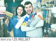Купить «Young joyous couple demonstrating tools for house renovating in paint store», фото № 25982267, снято 9 марта 2017 г. (c) Яков Филимонов / Фотобанк Лори