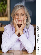 Купить «Portrait of worried senior woman sitting at table», фото № 25995591, снято 27 января 2017 г. (c) Wavebreak Media / Фотобанк Лори
