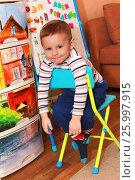 Купить «Маленький ребенок сидит на стульчике», фото № 25997915, снято 29 марта 2017 г. (c) Виктор Топорков / Фотобанк Лори