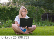 Pretty blonde woman with computer and book in the garden in sunny day. Стоковое фото, фотограф Александр Новиков / Фотобанк Лори