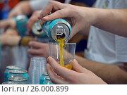 Купить «Пиво из алюминиевой банки наливают в прозрачный пластиковый стакан на дегустации напитка», фото № 26000899, снято 1 марта 2017 г. (c) Александр Замараев / Фотобанк Лори