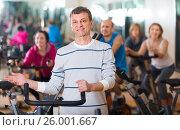 Купить «Man on fitness cycle training», фото № 26001667, снято 15 августа 2018 г. (c) Яков Филимонов / Фотобанк Лори