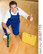 Купить «Happy handyman placing floor during renewal», фото № 26007715, снято 26 марта 2019 г. (c) Яков Филимонов / Фотобанк Лори