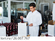 Купить «Man standing in packing section on winemaking factory», фото № 26007767, снято 21 сентября 2016 г. (c) Яков Филимонов / Фотобанк Лори
