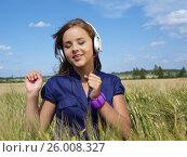 Купить «Teenage girl in a field listening music», фото № 26008327, снято 31 июля 2010 г. (c) Tatjana Romanova / Фотобанк Лори