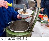 Купить «Повар накладывает порцию гречневой каши из армейского термоса», фото № 26008543, снято 9 апреля 2017 г. (c) Вячеслав Палес / Фотобанк Лори