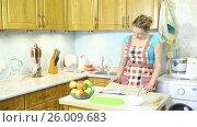 Купить «Светловолосая девушка в фартуке на кухне перед столом с яблоками изучает книгу рецептов», видеоролик № 26009683, снято 5 марта 2017 г. (c) Сергей Дубров / Фотобанк Лори