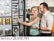 Купить «Couple next to showcase with door handles», фото № 26010751, снято 22 октября 2019 г. (c) Яков Филимонов / Фотобанк Лори
